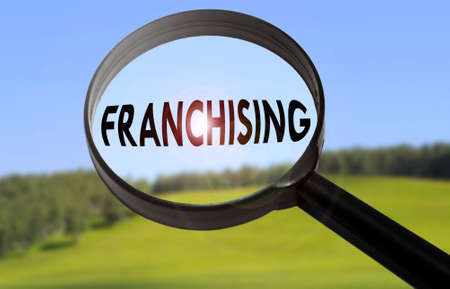 franchising: Magnifying glass with the word franchising on blurred nature background. Searching franchising concept