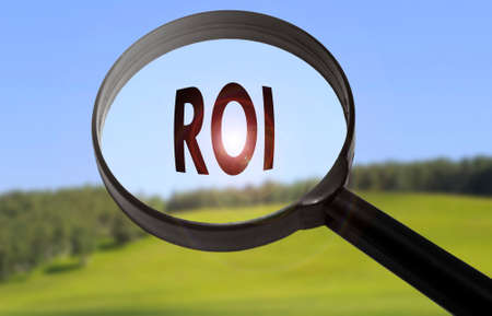 Magnifying glass with the word ROI (return on investment) on blurred nature background. Searching ROI (return on investment) concept