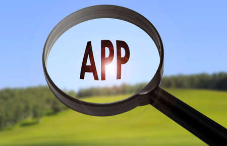 Magnifying glass with the word app (application) on blurred nature background. Searching app (application) concept