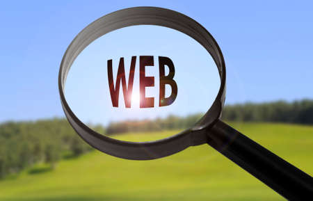 webmaster: Magnifying glass with the word web on blurred nature background. Searching web concept