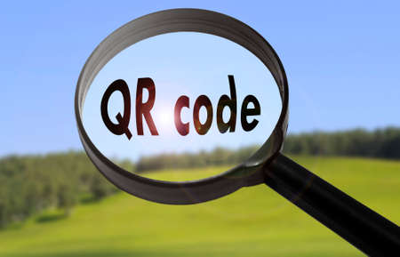 Magnifying glass with the word qr code (barcode) on blurred nature background. Searching qr code (barcode) concept