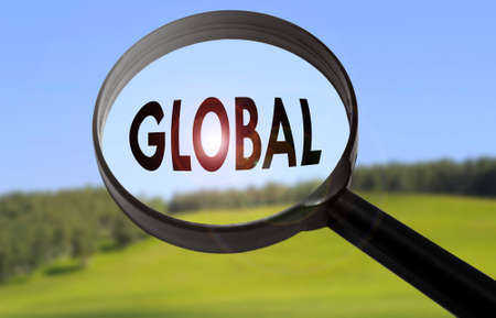 Magnifying glass with the word global on blurred nature background. Searching global concept