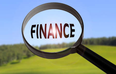 Magnifying glass with the word finance on blurred nature background. Searching finance concept
