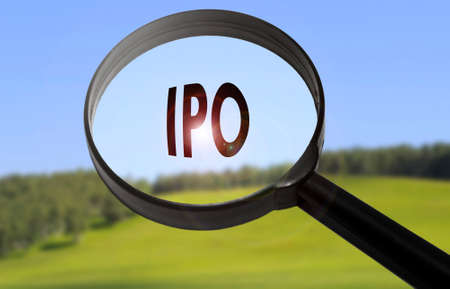 insider: Magnifying glass with the word IPO (initial public offering) on blurred nature background. Searching IPO (initial public offering) concept Stock Photo