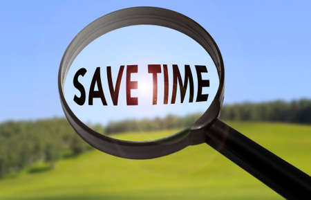 save time: Magnifying glass with the word save time on blurred nature background. Searching save time concept