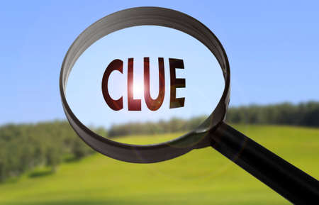 clue: Magnifying glass with the word clue on blurred nature background. Searching clue concept