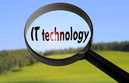 it technology: Magnifying glass with the word IT technology on blurred nature background. Searching IT technology concept Stock Photo