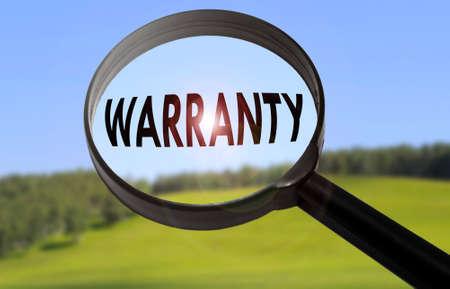 validez: Lupa con la palabra garantía en la naturaleza de fondo borroso. Búsqueda de concepto de garantía