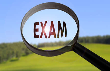 Magnifying glass with the word exam on blurred nature background. Searching exam concept Stock Photo