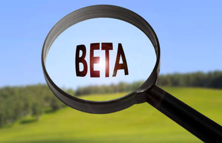 beta: Magnifying glass with the word beta on blurred nature background. Searching beta concept Stock Photo