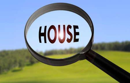 luxacion: Lupa con la palabra casa en el fondo la naturaleza borrosa. Búsqueda de concepto de casa
