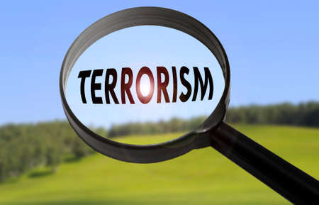 Magnifying glass with the word terrorism on blurred nature background. Searching terrorism concept Stock Photo