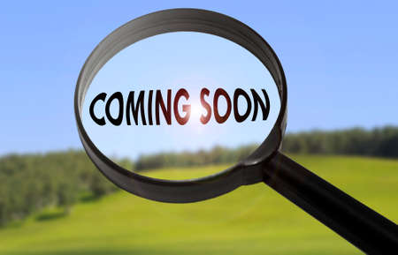 happening: Magnifying glass with the word coming soon on blurred nature background. Searching coming soon concept Stock Photo
