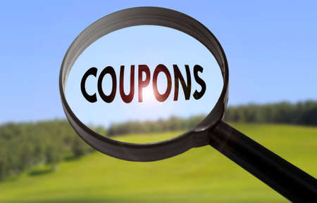 Magnifying glass with the word coupons on blurred nature background. Searching coupons concept Stock Photo