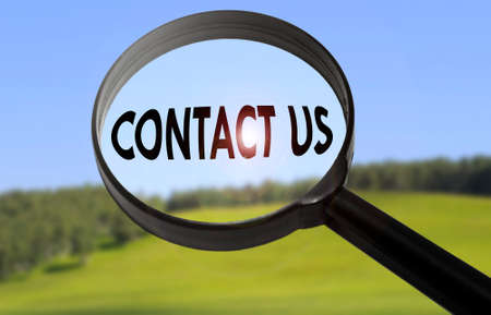 Magnifying glass with the word contact us on blurred nature background. Searching contact us concept Stock Photo