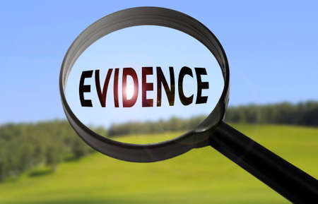 evidence: Magnifying glass with the word evidence on blurred nature background. Searching evidence concept