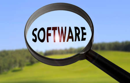 mysql: Magnifying glass with the word software on blurred nature background. Searching software concept