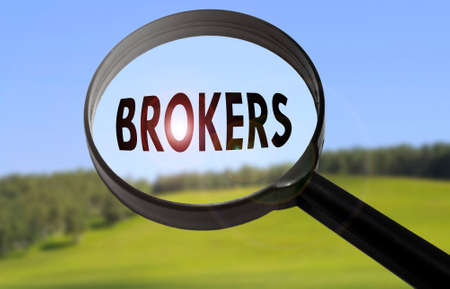 broker's: Magnifying glass with the word brokers on blurred nature background. Searching brokers concept