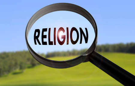 Magnifying glass with the word religion on blurred nature background. Searching religion concept