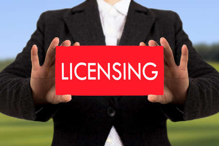 licensing: Businesswoman in a black jacket shows a card with the inscription licensing. Selective focus.