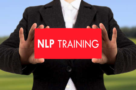 Businesswoman in a black jacket shows a card with the inscription nlp training. Selective focus. Stock Photo