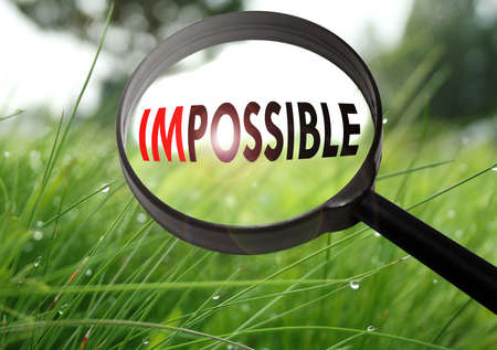 Magnifying glass with the word impossible on grass background. Selective focus Stock Photo