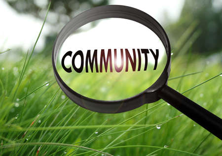 Magnifying glass with the word community on grass background. Selective focus Stock Photo