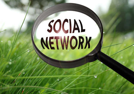 Magnifying glass with the word social network on grass background. Selective focus