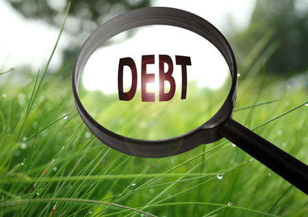 eliminating: Magnifying glass with the word debt on grass background. Selective focus Stock Photo