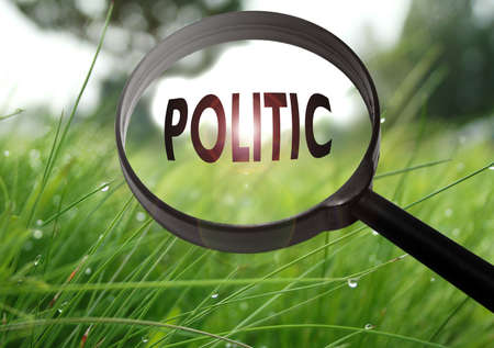 politic: Magnifying glass with the word politic on grass background. Selective focus