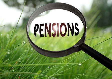 subsidize: Magnifying glass with the word pensions on grass background. Selective focus