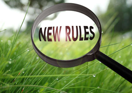 new rules: Magnifying glass with the word new rules on grass background. Selective focus