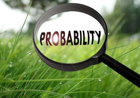 Magnifying glass with the word probability on grass background. Selective focus