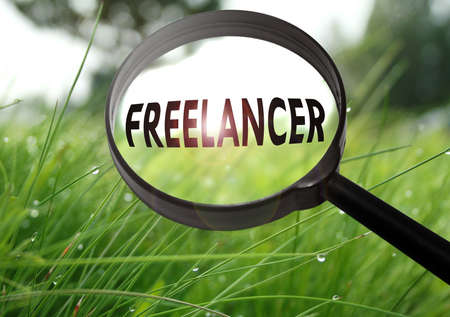 Magnifying glass with the word freelancer on grass background. Selective focus Stock Photo