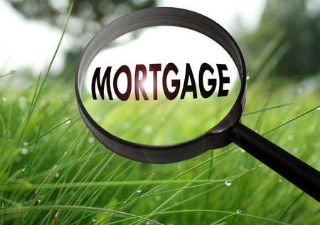 Magnifying glass with the word mortgage on grass background. Selective focus Stock Photo