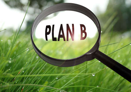 plan b: Magnifying glass with the word plan b on grass background. Selective focus