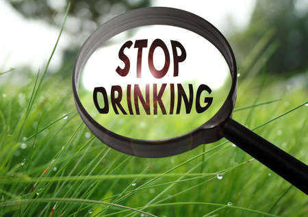 impaired: Magnifying glass with the word stop drinking on grass background. Selective focus