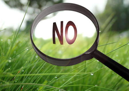 negation: Magnifying glass with the word no on grass background. Selective focus