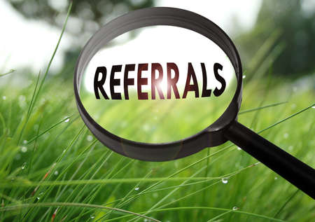 Magnifying glass with the word referrals on grass background. Selective focus
