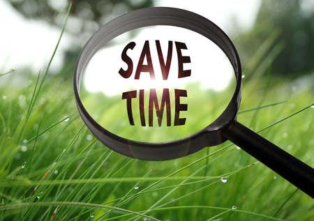 cronologia: Lupa con la palabra ganar tiempo en el fondo de hierba. enfoque selectivo Foto de archivo