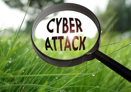 Magnifying glass with the word cyber attack on grass background. Selective focus Stock Photo