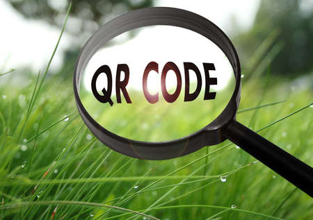 Magnifying glass with the word qr code (barcode) on grass background. Selective focus