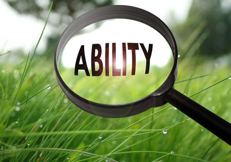 Magnifying glass with the word ability on grass background. Selective focus