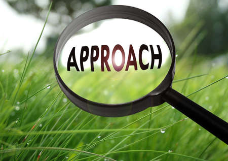 Magnifying glass with the word approach on grass background. Selective focus Stock Photo