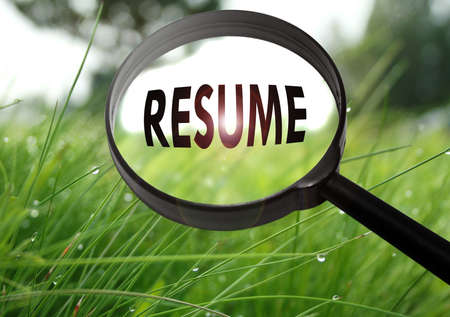 job qualifications: Magnifying glass with the word resume on grass background. Selective focus