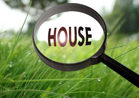 luxacion: Magnifying glass with the word house on grass background. Selective focus
