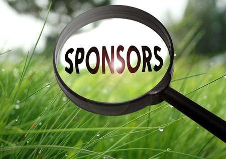 Loupe avec le mot sponsors sur le fond de l'herbe. Focus sélectif