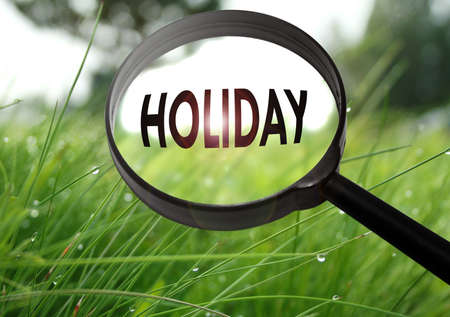 Magnifying glass with the word holiday on grass background. Selective focus