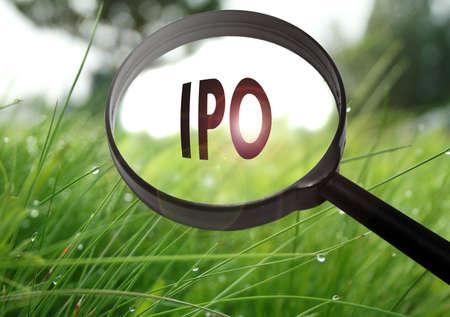 잔디 배경에 단어 IPO (기업 공개)와 돋보기. 선택적 포커스