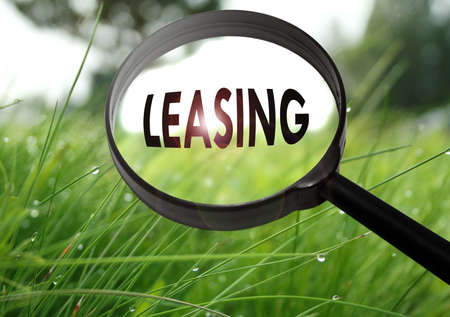 leasing: Magnifying glass with the word leasing on grass background. Selective focus Stock Photo